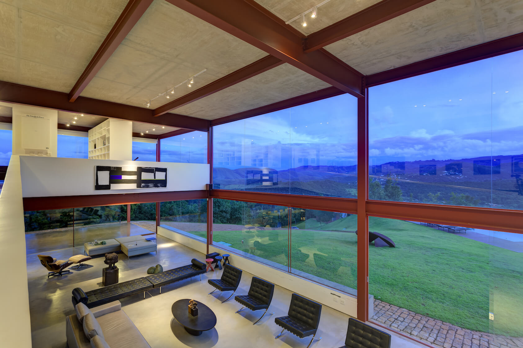 From the top of the ramp, we see down onto the array of modern leather seating options and the stone path surrounding the home.