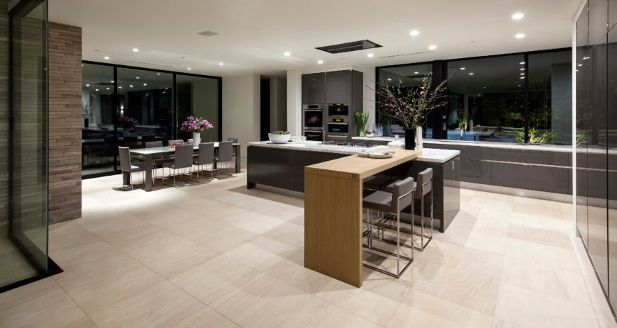 The kitchen features a grand dual-section island, with main body in dark cabinetry and white marble countertop plus natural wood dining space extension. Slate grey cabinetry abounds throughout, matching the dining set on left.