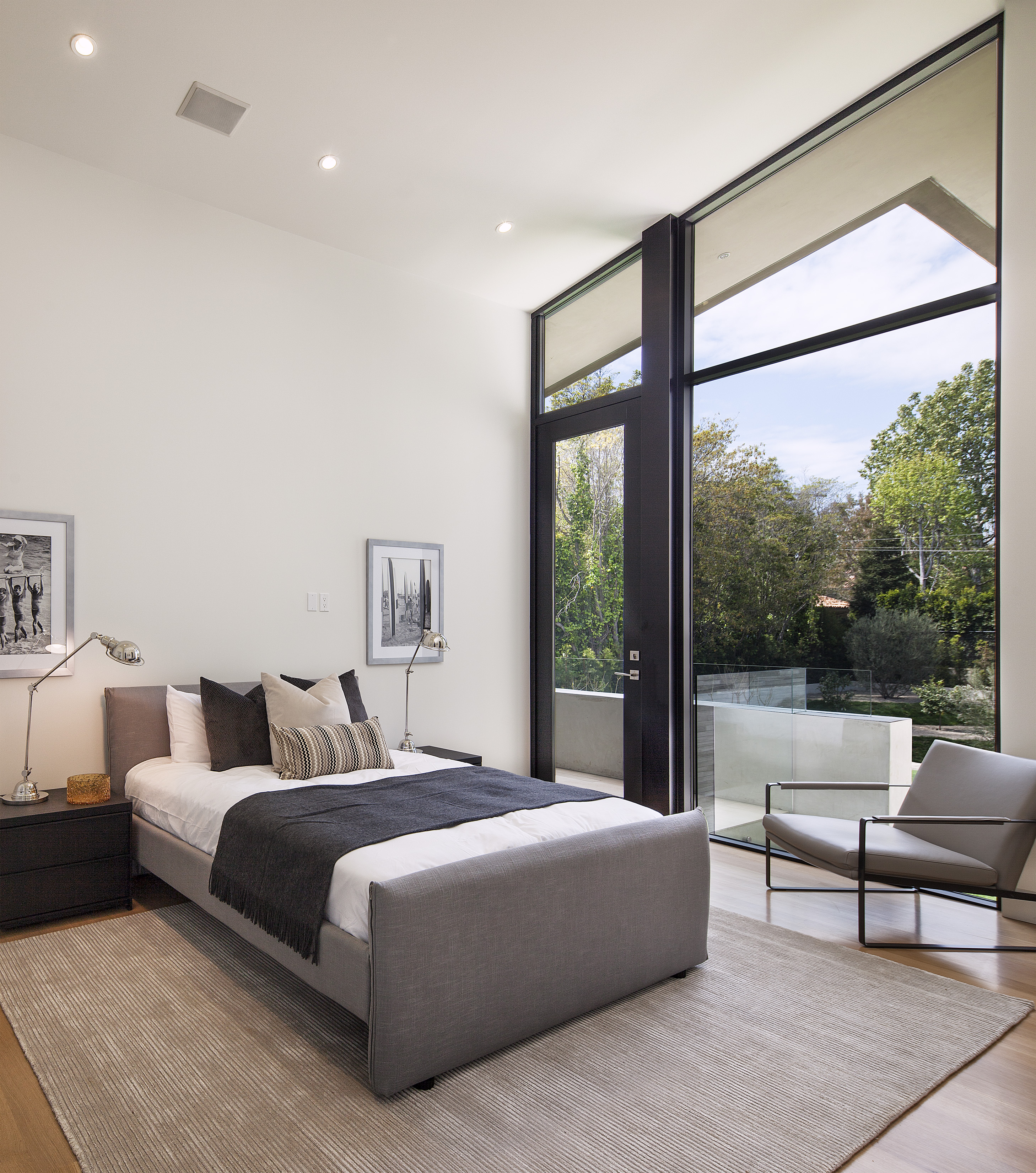 Bedroom continues the grey and natural wood motif of the upper floor, with glass patio door allowing for private balcony space.