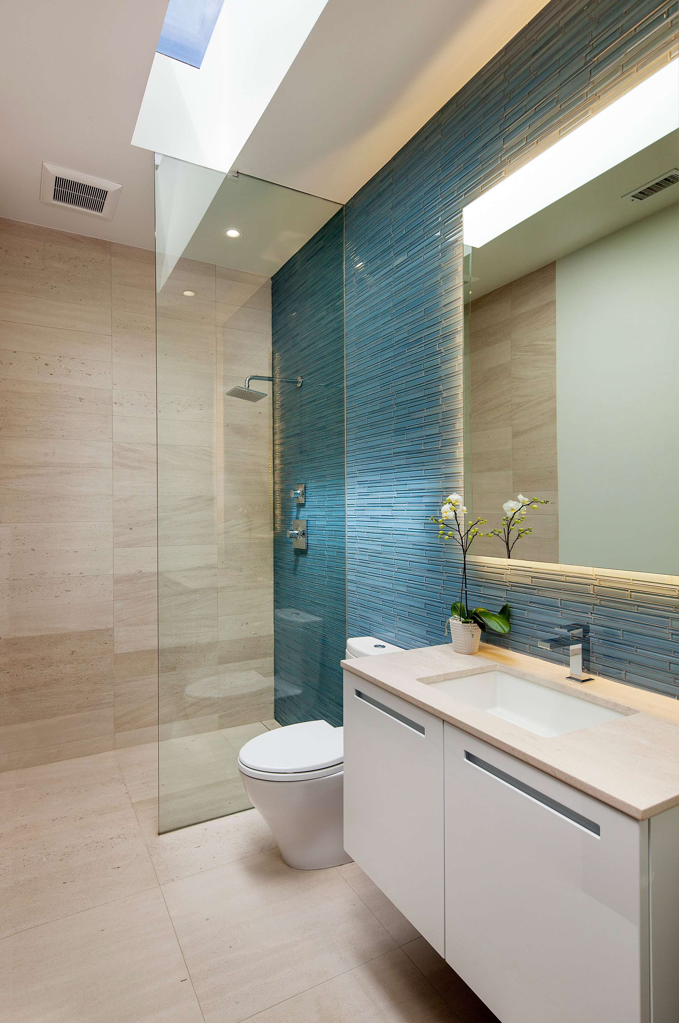 Bathroom features another novel tone: narrow blue tile across vanity wall breaks up the neutral tones. Marble topped counter and seamless glass shower stand below sky light slit.