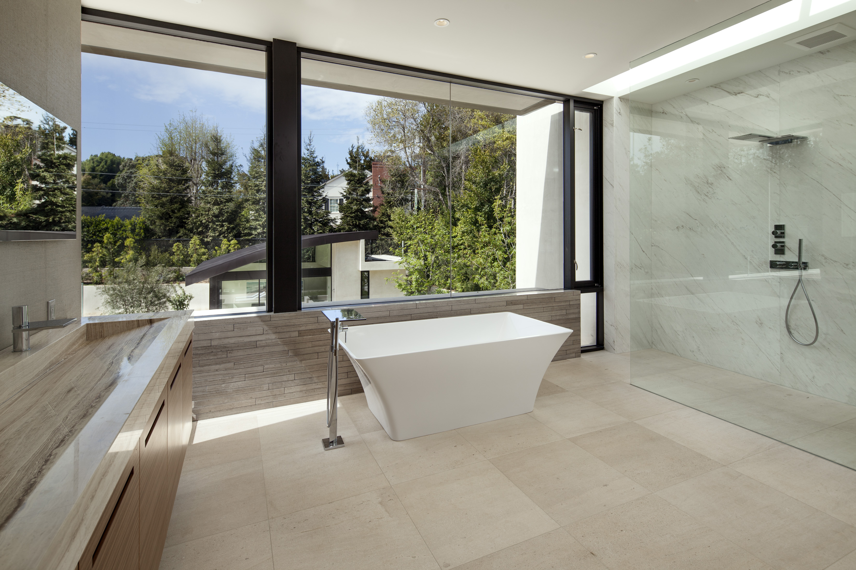 Primary bath contains a lengthy marble trough-style sink, white pedestal tub basking in natural light, and massive walk-in glass shower on right.