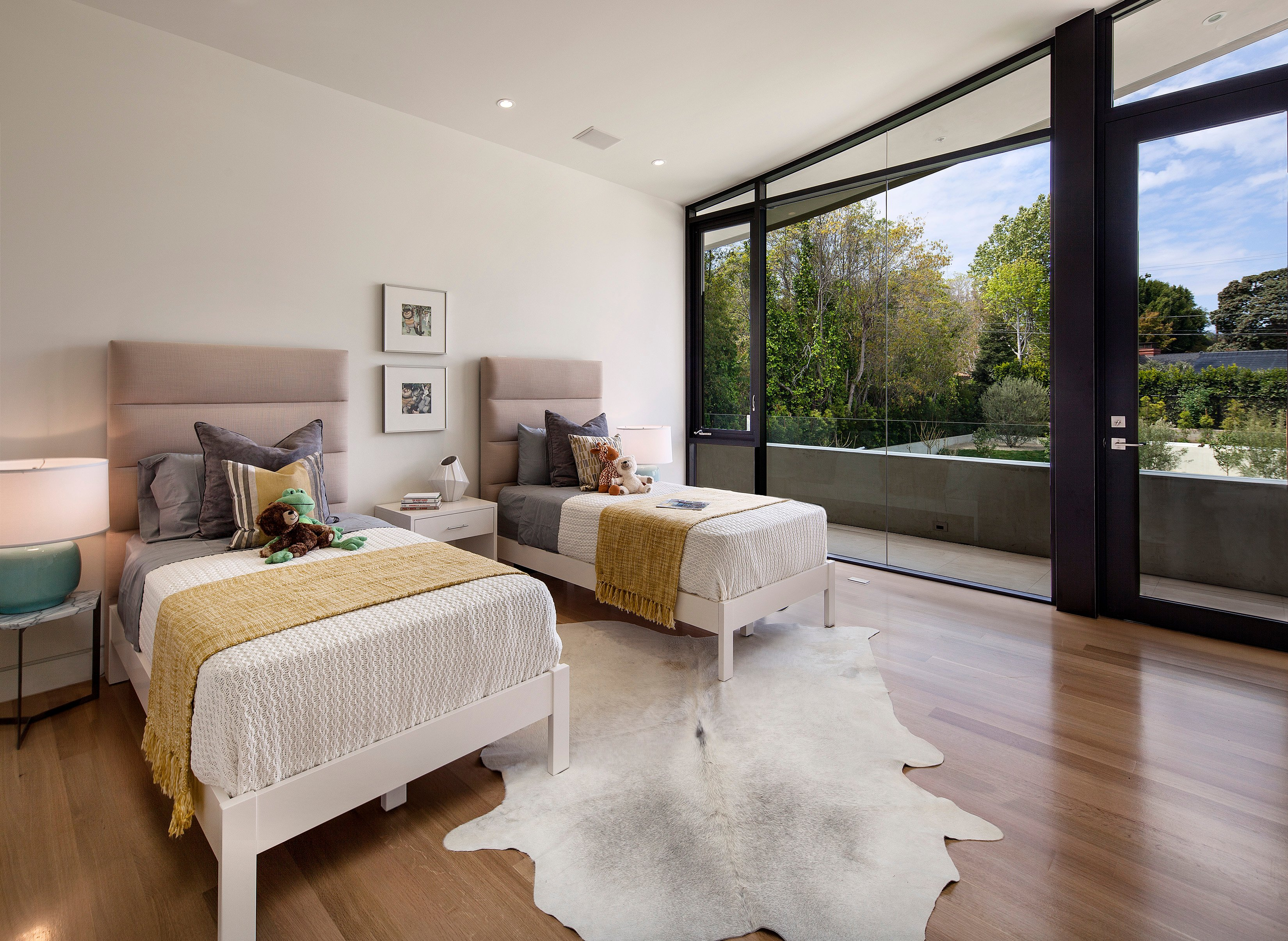 Upper level children's bedroom pairs white wood framed beds over animal skin rug on the same natural hardwood flooring deployed throughout the second floor. Once again, glass exterior wall and door open to private balcony space.