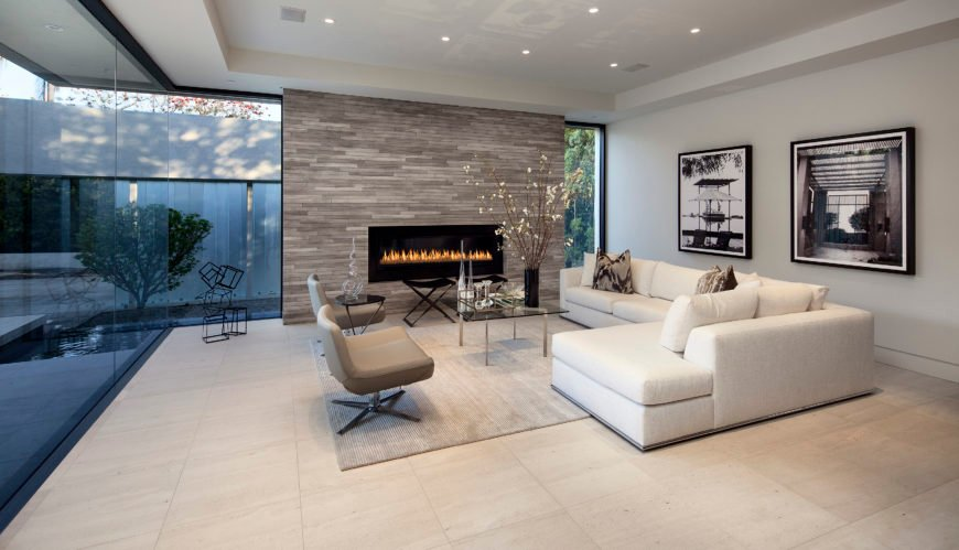 Front living room space involves a similar arrangement of white sectional, twin chairs, and coffee table set before wide gas fireplace with floor to ceiling brick surround.