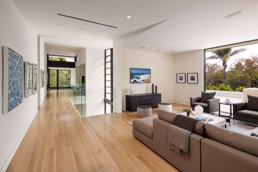 Upper floor spreads opulence over natural hardwood flooring, with a range of mocha furniture pieces and glass framed catwalk overlooking main entrance.