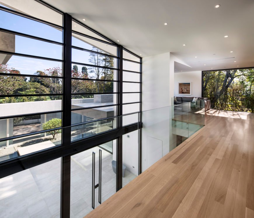 Here's a close view of the all-glass front entrance from the second floor catwalk. Views of surrounding nature through floor to ceiling glass abound, and enclosed courtyard is seen on left.