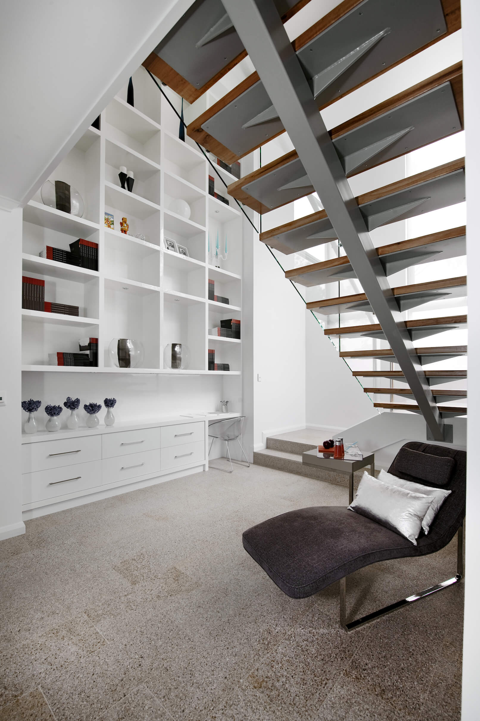 This angle shows more of the giant, two story bookshelf built into the structure, with desk surface at bottom and series of sectioned shelving extending upwards.