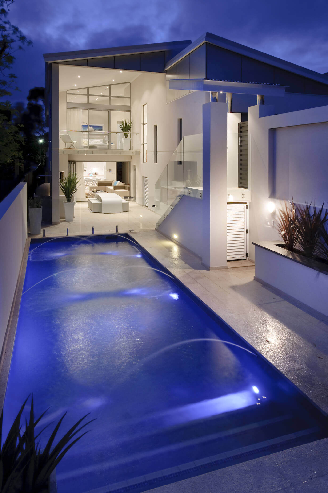 Courtyard holds massive fountain-equipped pool, wrapped with patio extending from the home interior through full height glass. Both patios have expansive view over this space, while rear gate at right provides stair entryway for guests.