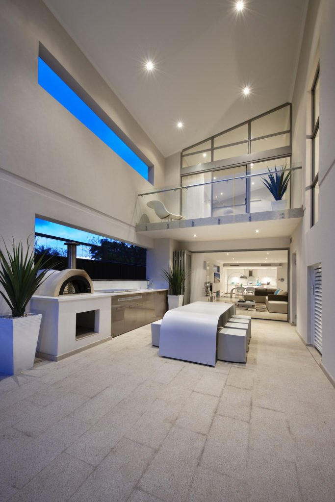 Patio features a second arched white dining table, with full kitchen style counter and built-in grill at left, beneath second floor private balcony.