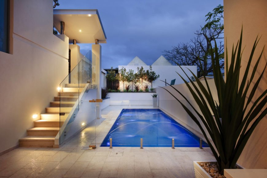 View from the lower level patio, revealing all-glass dividing wall separating the pool space. Privacy wall wraps the entire rear exterior of the home.