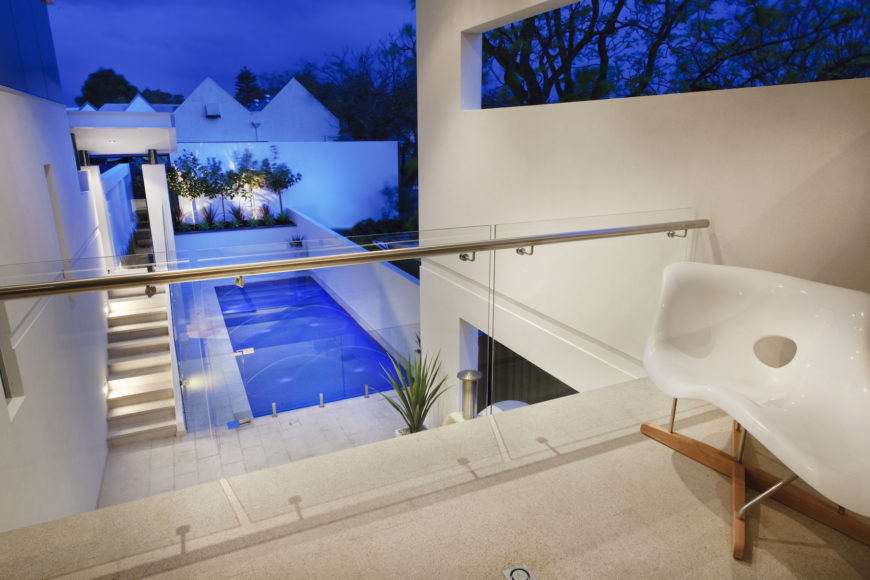 This view, from the upper level private balcony, reveals more of the metal and glass railings that allow for ample views through multiple layers of the home. Unique amorphous white plastic and natural wood chair sits on the right.