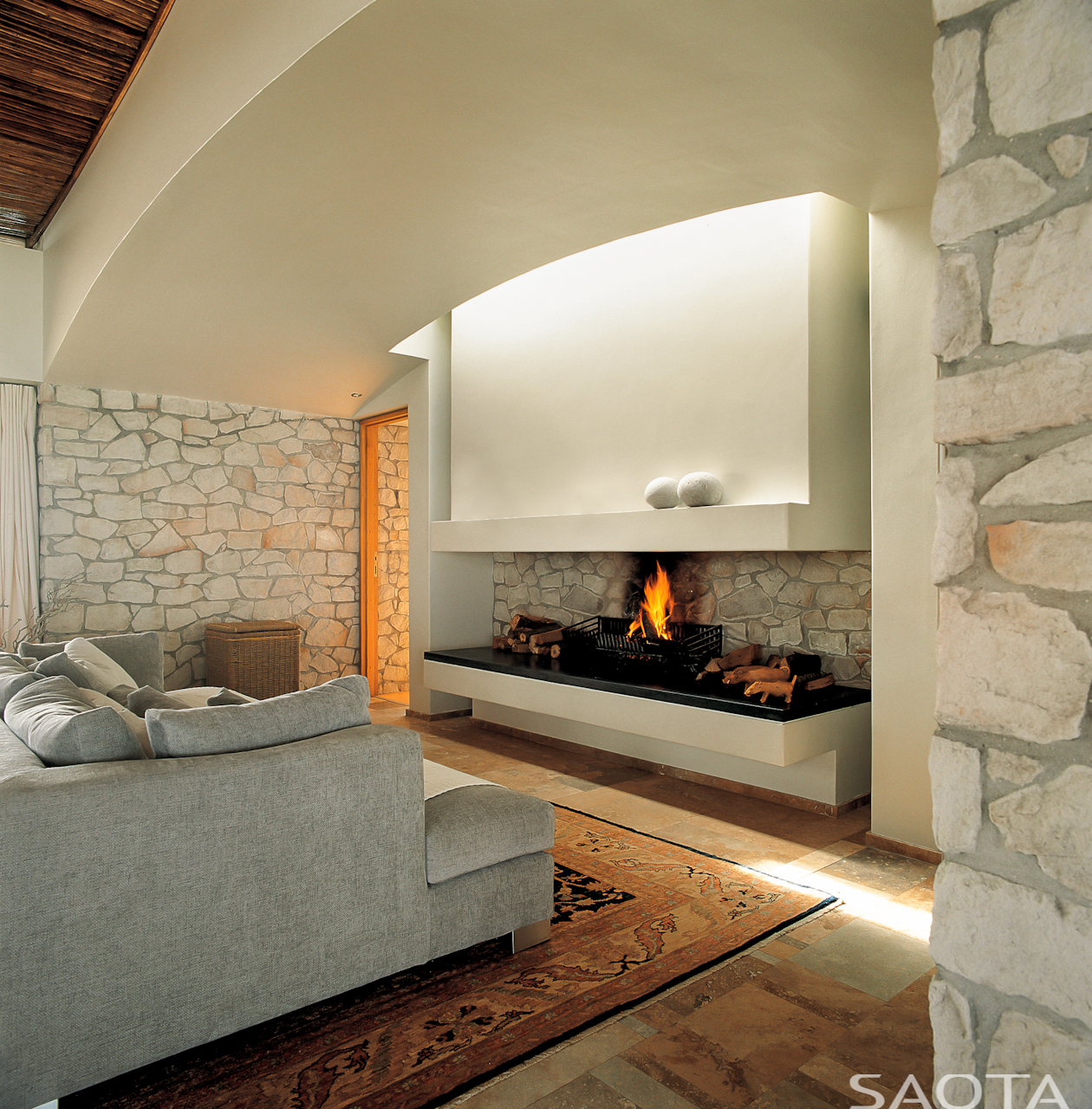 Close view of the fireplace. Open design allows fire to sit on built-in shelf, with hidden chimney behind white detail wall extension.