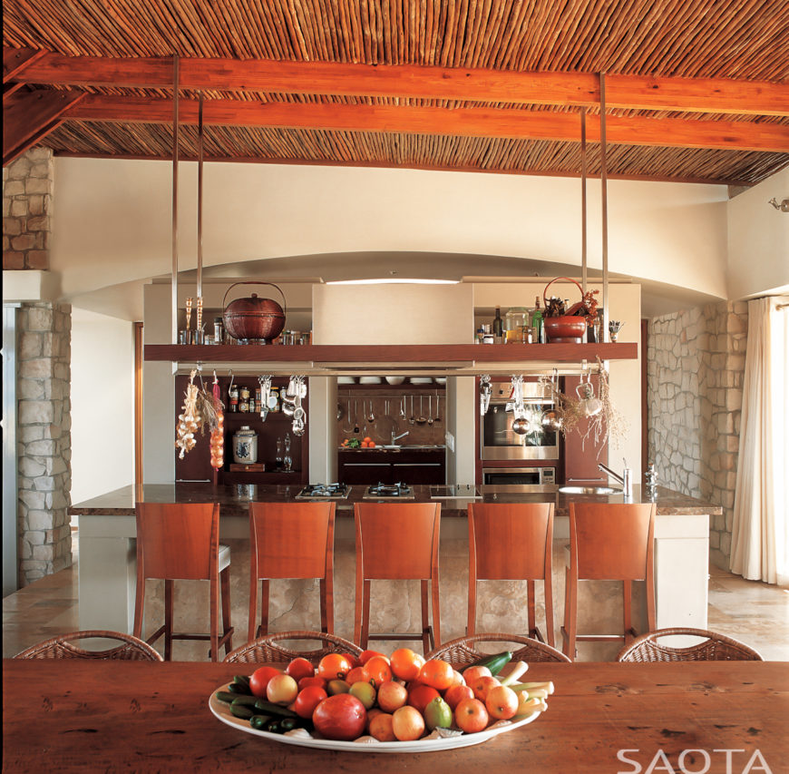 The thoroughly modern kitchen appears in timeless, traditional materials: natural wood stools at the large, marble topped island, sitting beneath hanging wooden shelving piece, suspended from exposed ceiling beams. Natural wood dining table appears in foreground.