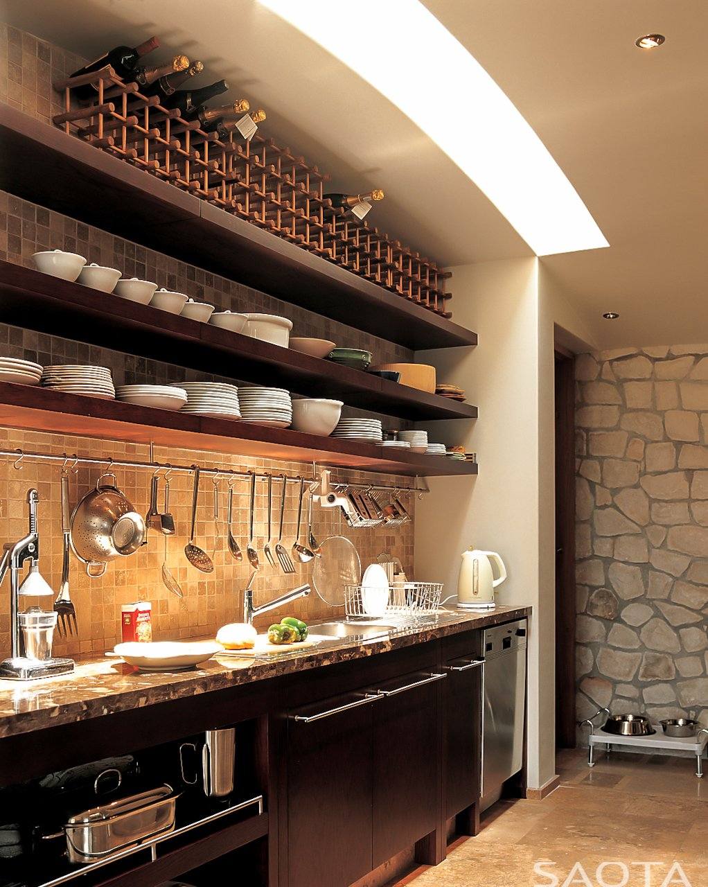 The main kitchen counter features dark marble over dark wood cabinetry, with built-in shelving above tile backsplash, including wine rack at top.