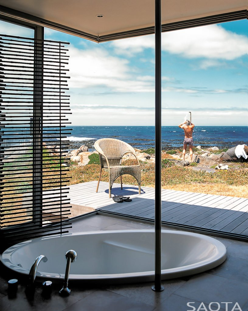Corner bathroom affords spectacular view of the ocean from the sunken bathtub. Patio extension and outdoor shower seen through the floor to ceiling glass.