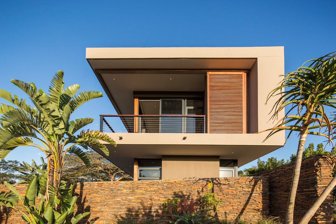 Side view reveals the C-shape of the structure, holding the glass-paneled rooms in protection from the elements.