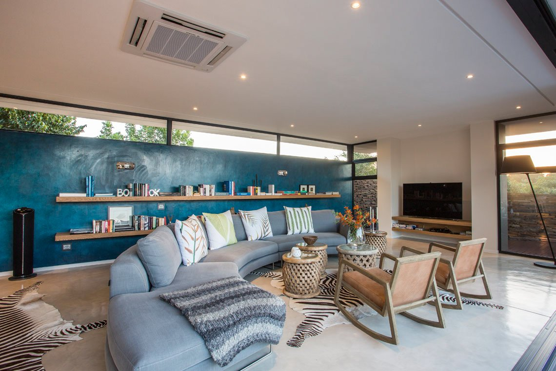 Living room features bold coloring, with blue wall holding lengthy mounted natural wood shelving, plus C-shaped sectional between pair of zebra skin rugs on white flooring. Upper level horizontal windows on front are seen.