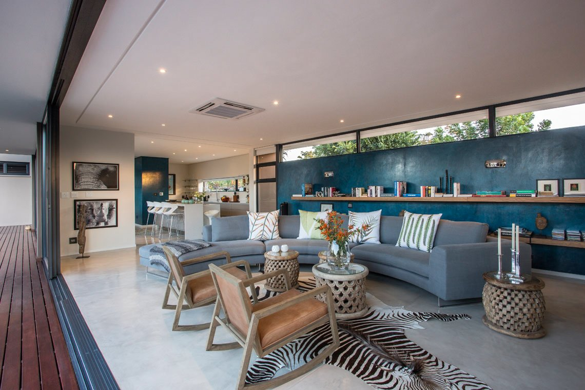Side view of the open plan living room, reveals kitchen space in background, plus glass sliding panels to back yard fully open, for seamless indoor-outdoor transition.