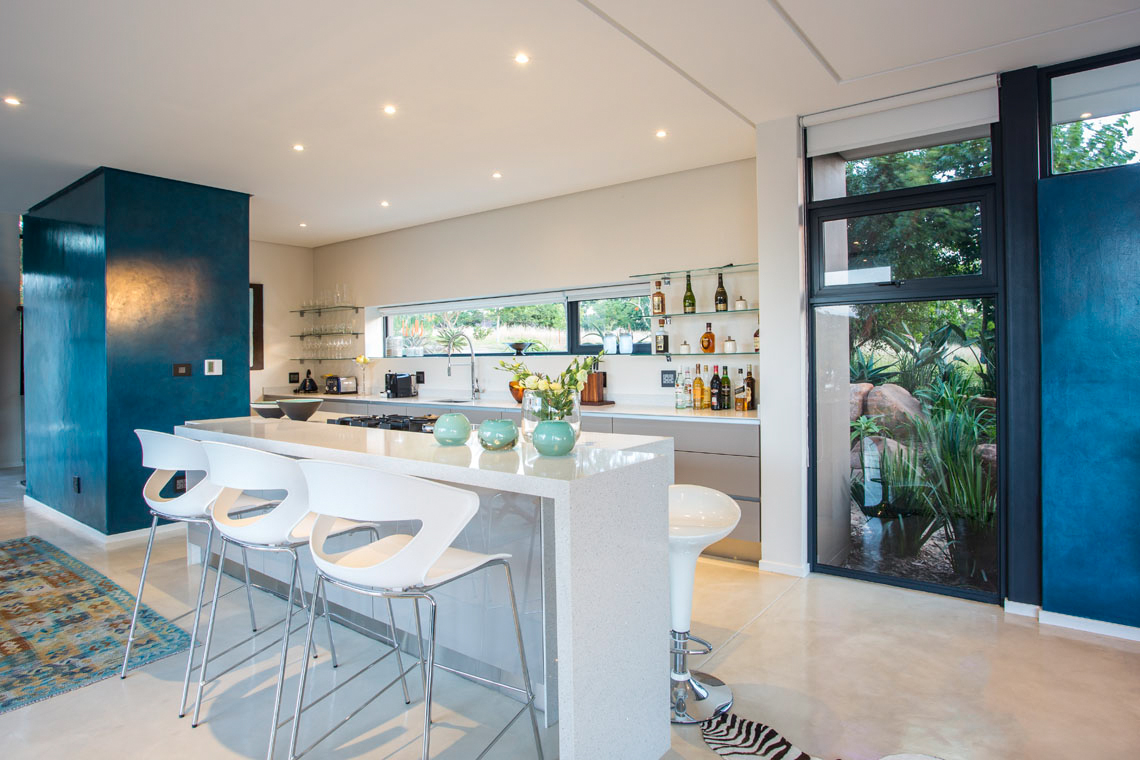 Kitchen features white marble countertops and island, with full range and dining space built in. Glass shelving flanks the horizontal window in background.