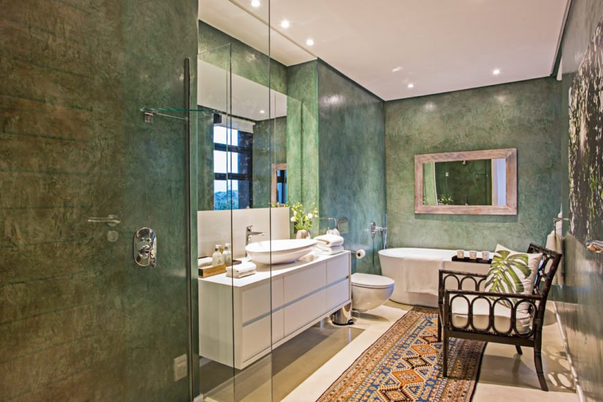 """This bathroom continues the forest green motif, housing a pedestal tub and """"floating' white vanity next to seamless glass shower."""