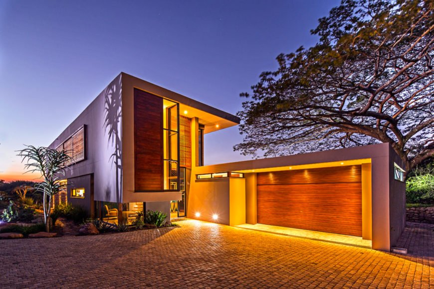 The garage, as seen at twilight. Warm under-eave lighting brightens every facade of the home, highlighting the natural wood paneling and garage door.