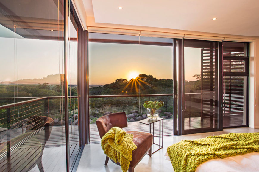Upper level corner bedroom is wrapped in floor to ceiling glass, affording expansive views of the surrounding countryside. Timber privacy panels are pushed to the right, while fully blocking window shades are rolled up.