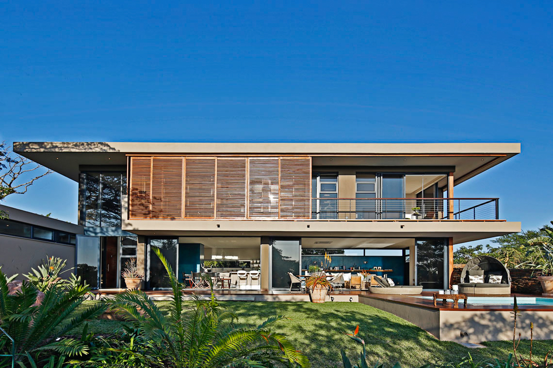 View of the home with sliding timber panels mostly shut, granting shade and privacy to upper level bedrooms.