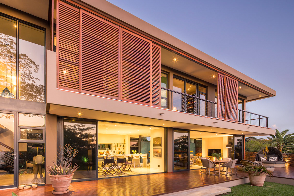 Interior glowing at dusk, with soft warm lighting extending to patio overhang.