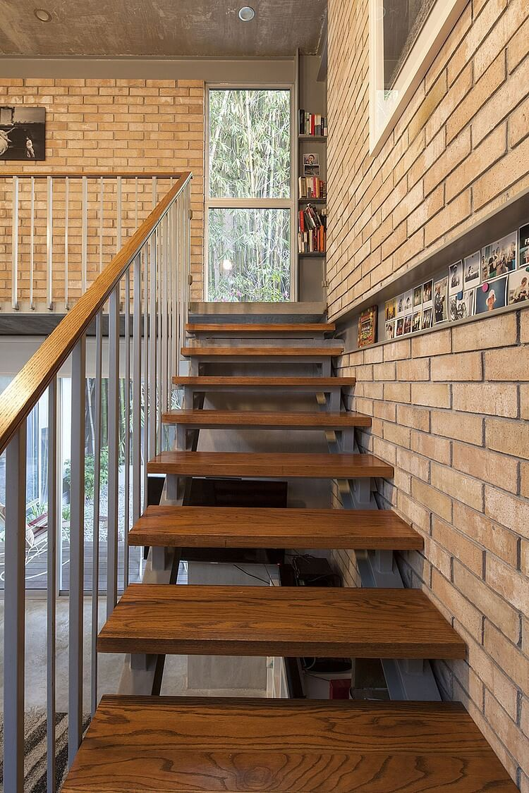 The steel and hardwood staircase features see-through gaps for more visual space. Next to the ceiling height window, we see shelving built into the metal structure.