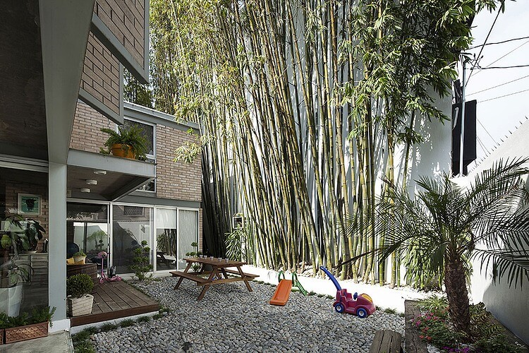The bamboo perimeter creates the illusion of forested surroundings, offering pleasant greenery in view from every window. Rock garden area is flattened for socializing and play.