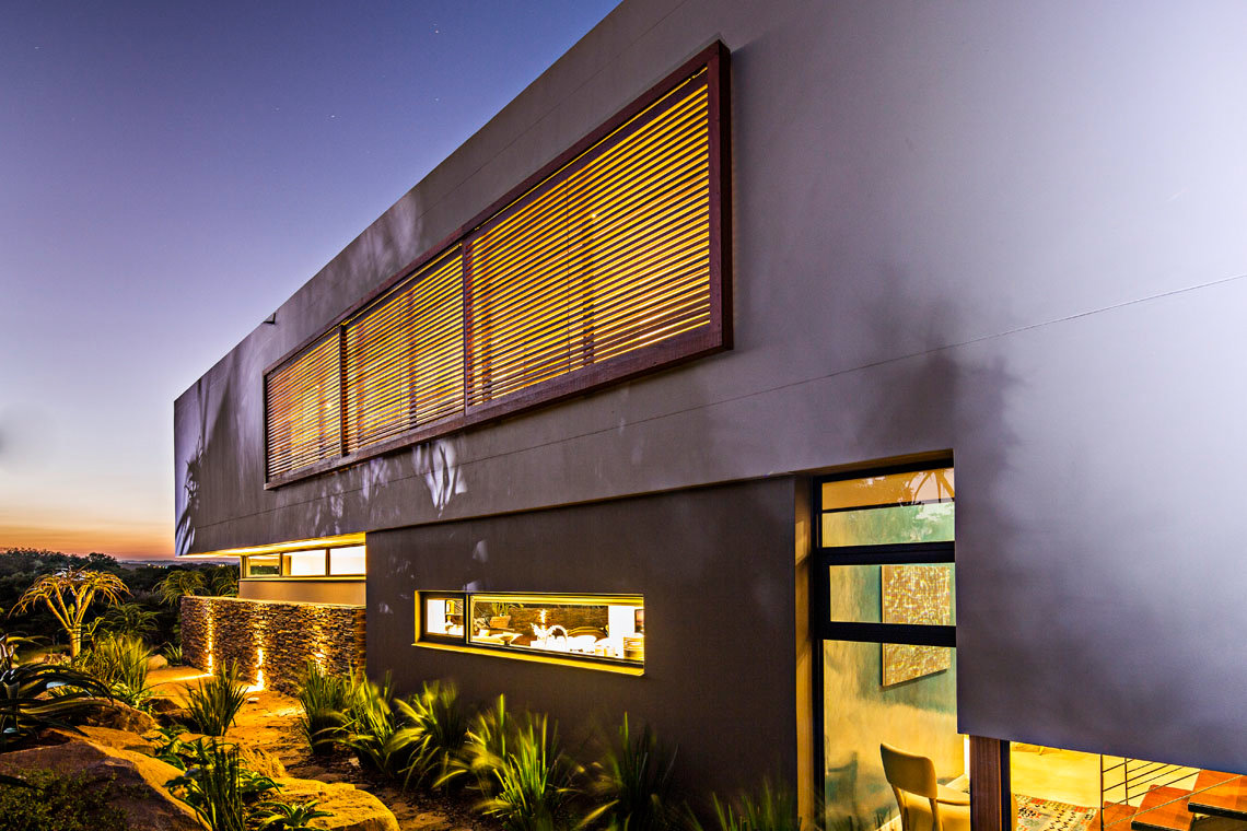 Front facade at night. Interior lighting glows through timber shades mirroring the sliding panels on the rear balcony.