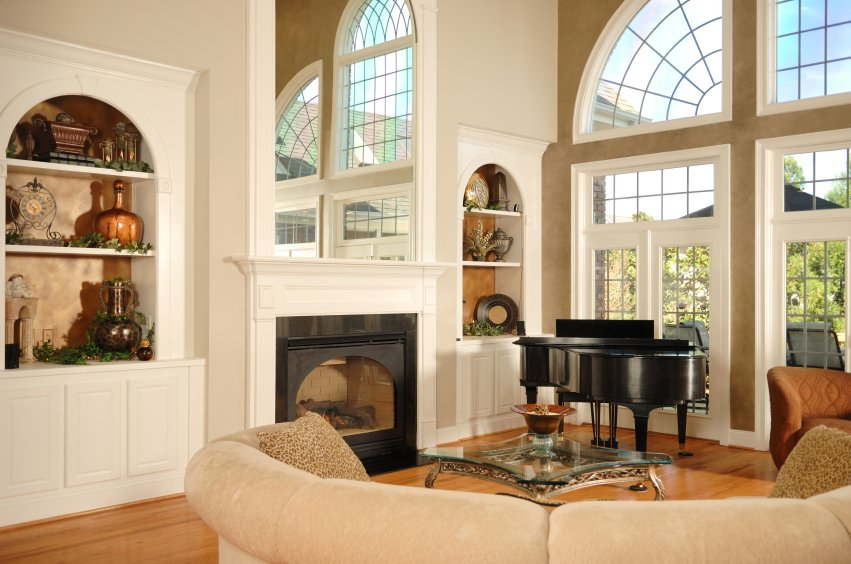 This living room features an immense mirror mounted over the fireplace, multiplying the natural light entering via full height windows at right. Hardwood flooring and beige tones surround detailed wall shelving and glass topped coffee table.