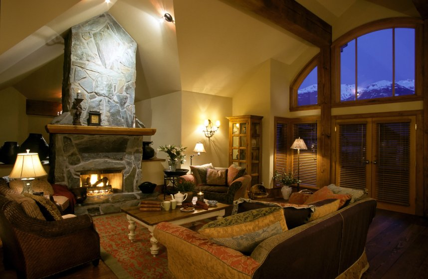 Cozy, rustic styled living room pairs natural wood throughout with free-standing stone fireplace. Plush furniture circles an arrow foot, hardwood topped coffee table.