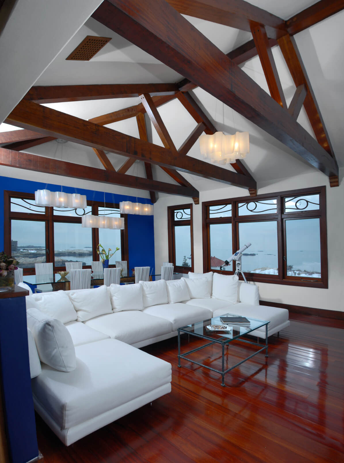 Bold mixture of dark hardwood flooring, white sectional, and blue wall details stand in this living room beneath vaulted, exposed beam ceiling.