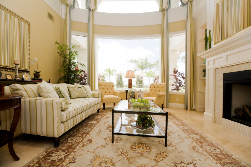 Here's a lower angle on the prior living room, highlighting the detailed area rug and glass coffee table and expansive windows.