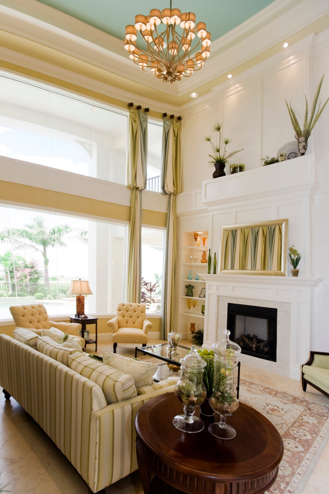 Bright yellow and white color scheme of this living room helps natural light illuminate the large space. Marble flooring, white tile fireplace surround, and carved wood tables join an array of citrus toned furniture.