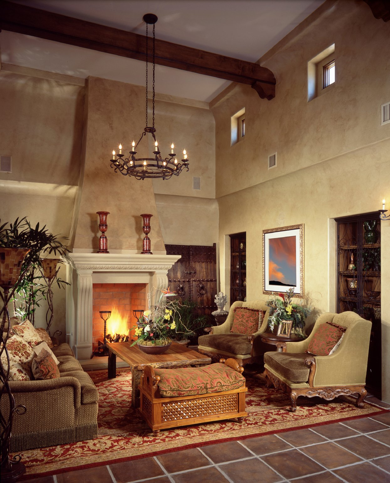 Tall yet cozy space here features natural carved wood coffee table surrounded by plush chairs and sofa and large white marble fireplace. Old fashioned chandelier hangs from exposed wood beam overhead, while red patterned area rug sits on brown tile flooring.