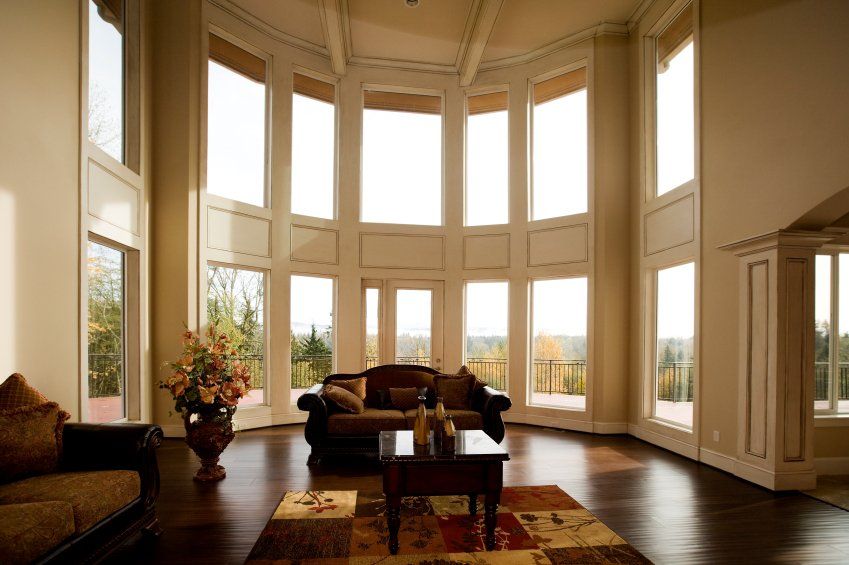 Immense, rounded living room is naturally lit via a curved array of two story windows. Dark hardwood flooring pairs with dark leather sofas and glass-topped coffee table over floral patterned rug.