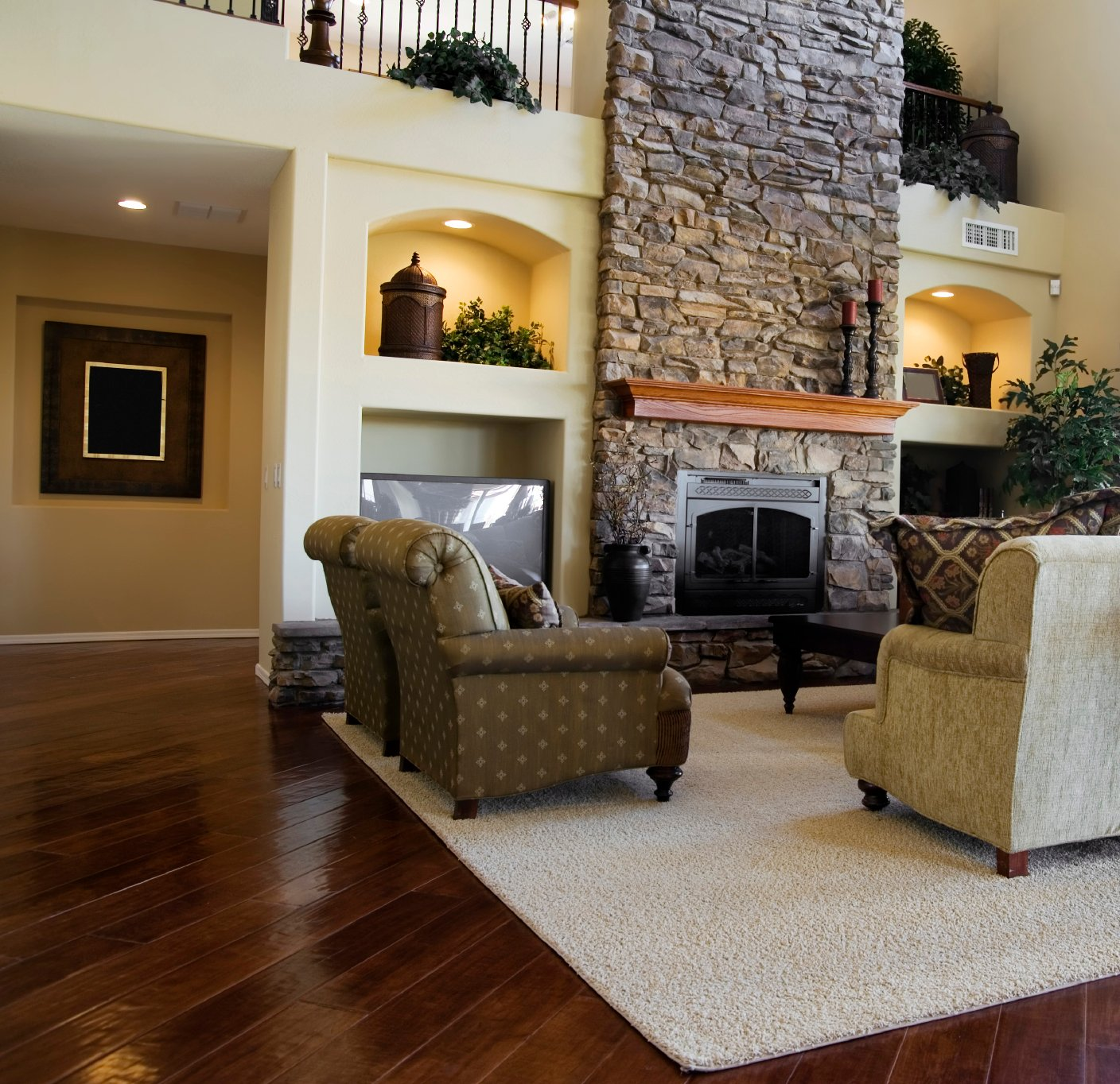 Another luxurious living room dominated by large stone fireplace, this room features dark hardwood flooring contrasting with light toned walls with built-in decorative shelving.