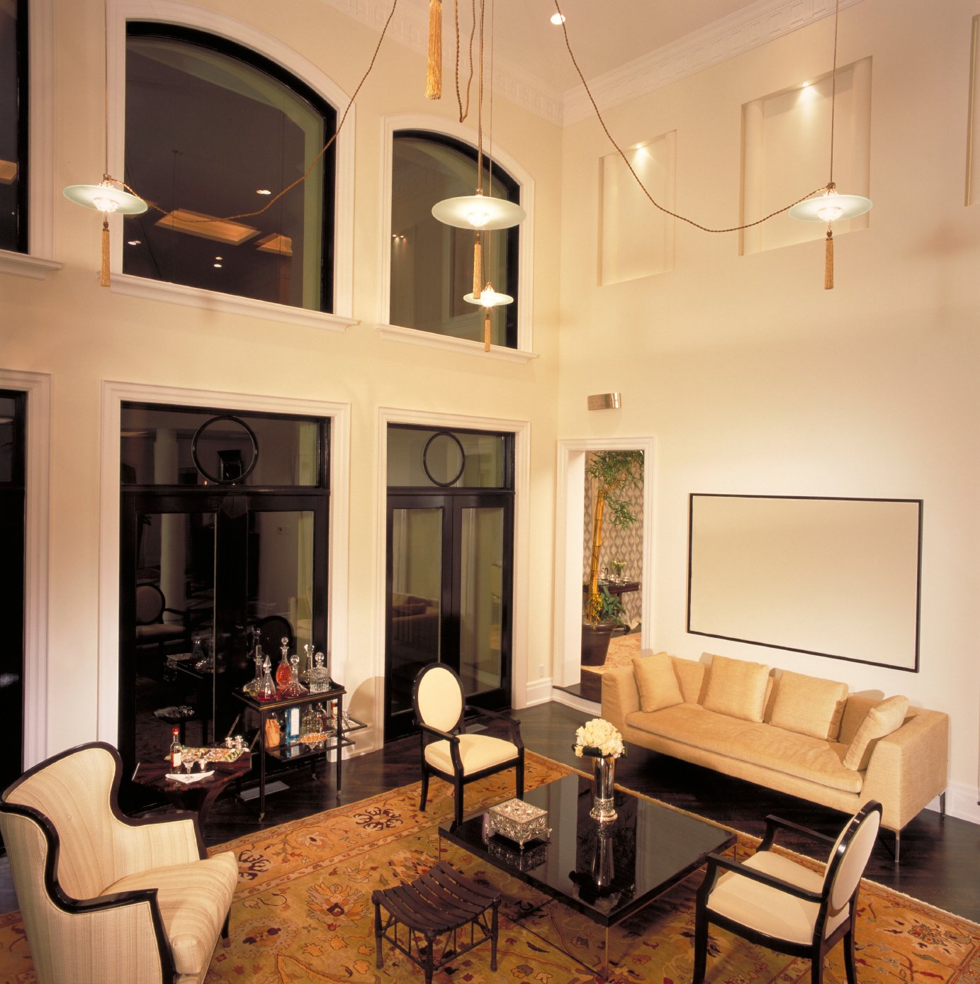 Striking details abound in this high contrast room, featuring dark hardwood flooring set against white walls and two stories of windows. Carved wood chairs and contemporary sofa sit around glossy black coffee table, unique four-part chandelier hangs above, and an array of glass patio doors stand at left.