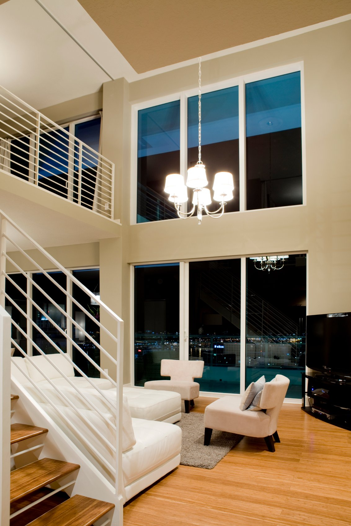 Minimalist, modern living room sets white furniture and beige wall tones against natural hardwood flooring and stairs, with an array of full height windows affording expansive views.