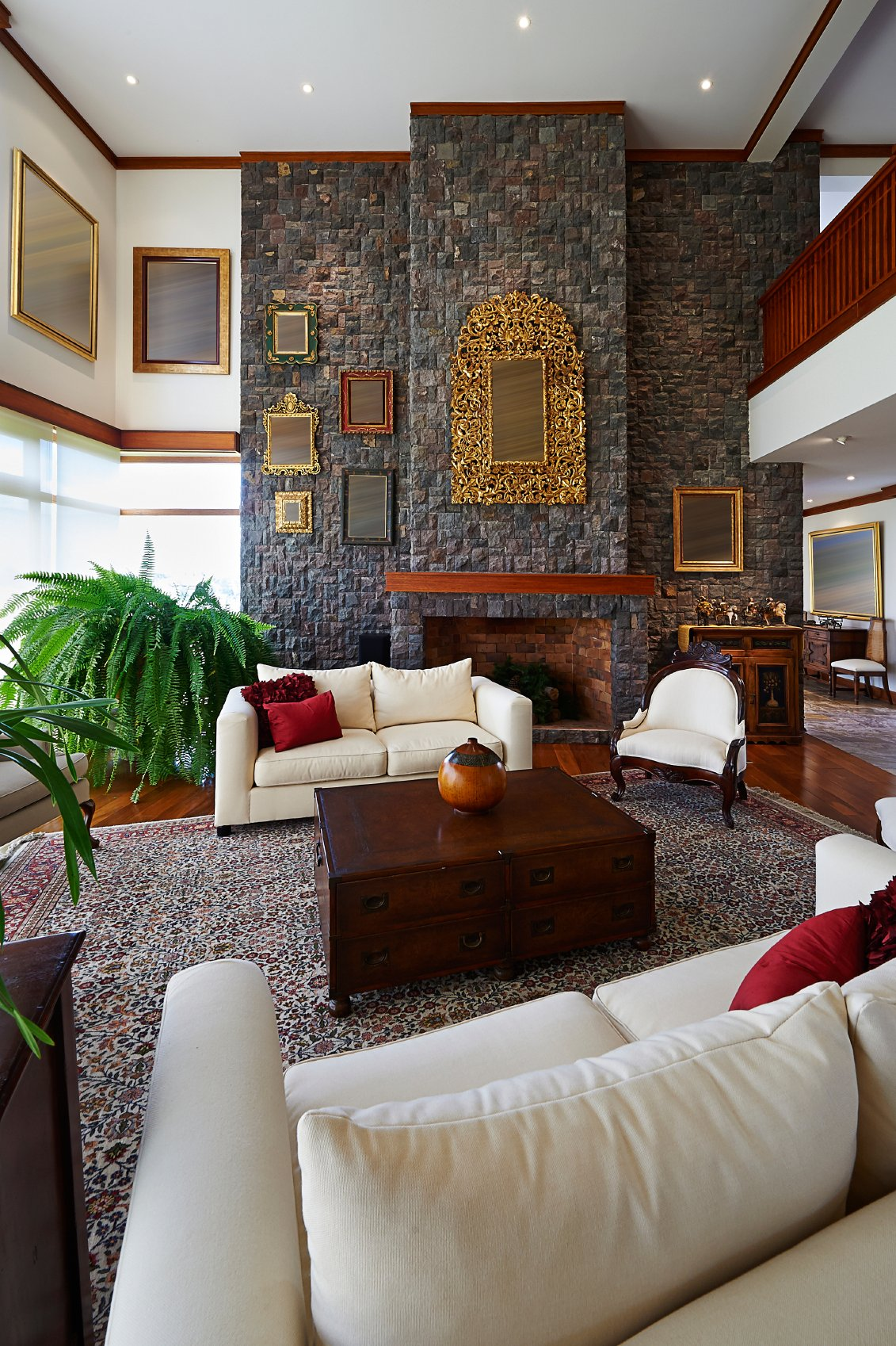 This luxurious room is dominated by massive stone fireplace wall, looming over a rich hardwood floor with large floral area rug and white and dark wood furniture. Gold details abound, framing paintings scattered throughout.