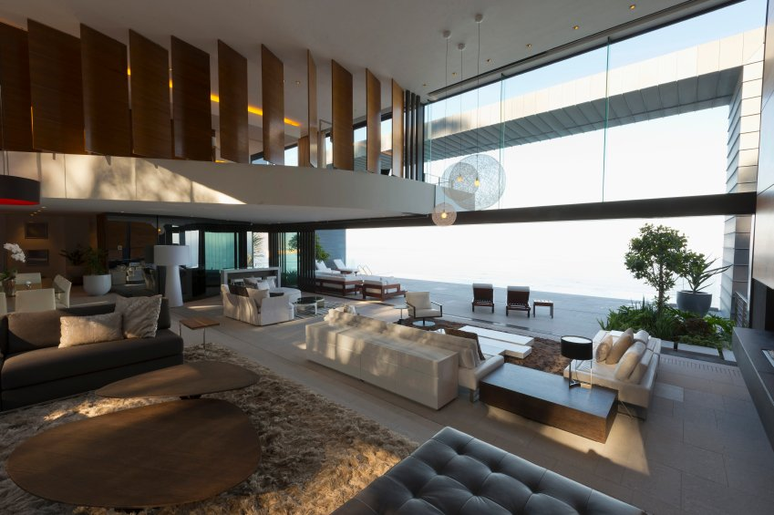 This sprawling living room opens fully to patio space with retractible glass panels. An array of white leather sofas and minimalist wood tables stand over white tile flooring, with brown area rug and oblong tables standing on left, beneath large artful wood-panel ceiling detail.