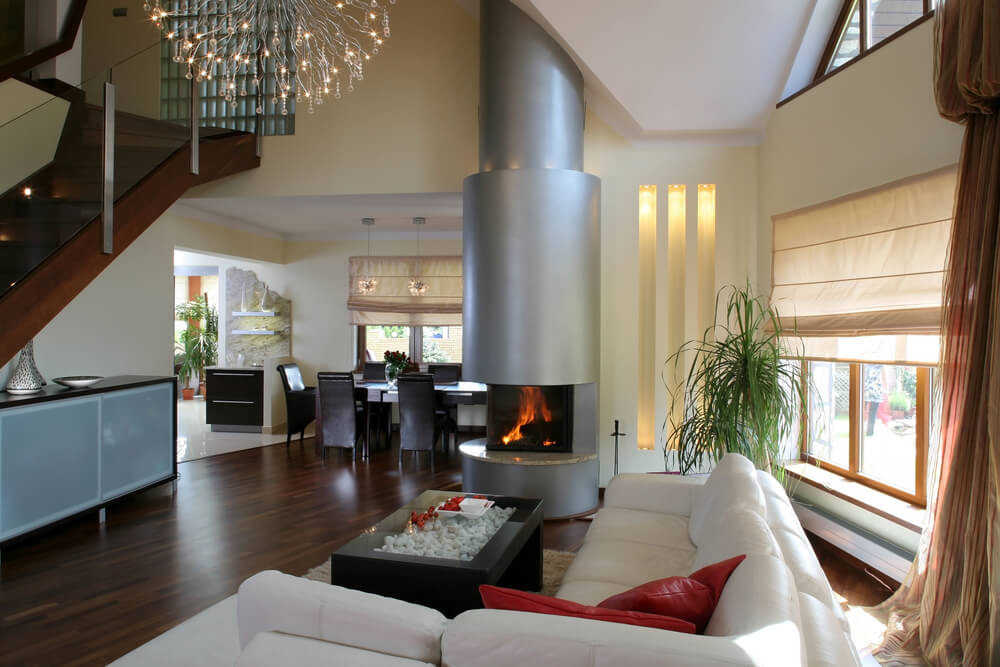 Here's a thoroughly modern living room filled with a variety of color and texture. White L-shaped sectional wraps around a unique glass-topped, white rock filled coffee table next to a cylindrical fireplace over an expanse of dark hardwood flooring.