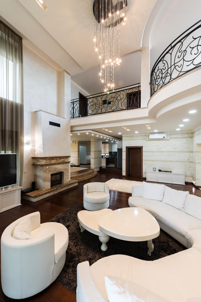 Lush two story living room in white stands over dark hardwood flooring, with balcony space overlooking. U-shaped white sectional and matching two-tier coffee table stand over thick brown rug, with marble fireplace standing across.
