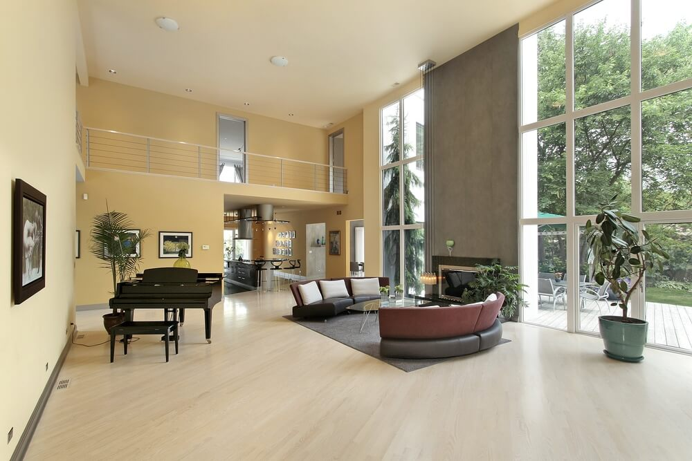 Immense rectangular living room features floor to ceiling exterior glass flanking an immense fireplace, with twin C-shaped sectionals paired over a glass topped coffee table. Catwalk with steel railings stands over kitchen entrance, overlooking the wide swath of light natural hardwood flooring.