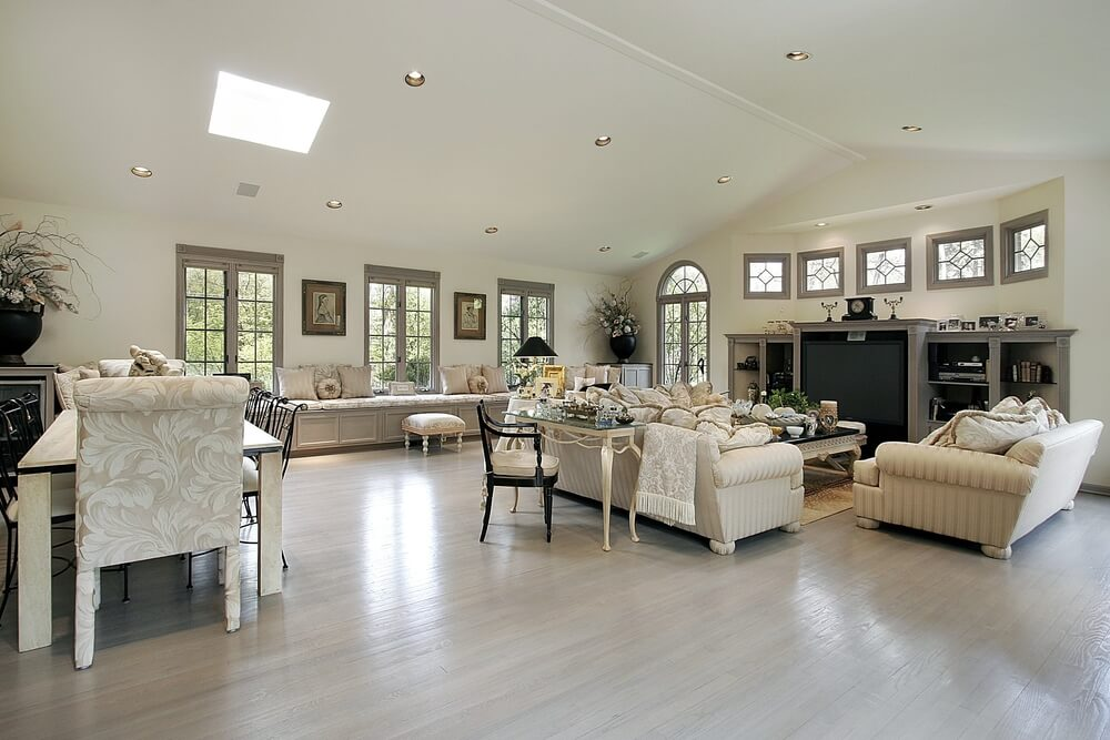 Wide open design living room awash in light neutral tones, with vaulted ceiling dotted with recessed lighting over an array of furniture sets in striped and patterned beige. Sofas center around large black topped coffee table, while daybed space runs length of the exterior wall.