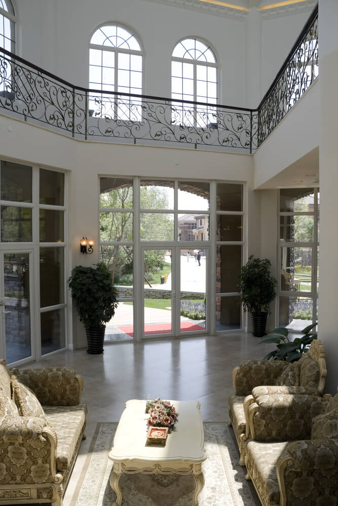 Wrapped in exterior glass, this marble floor living room is overlooked by a ring of upper level walkway. White surroundings are spiked with black wrought iron railings, with array of ornate, traditional furniture at center.