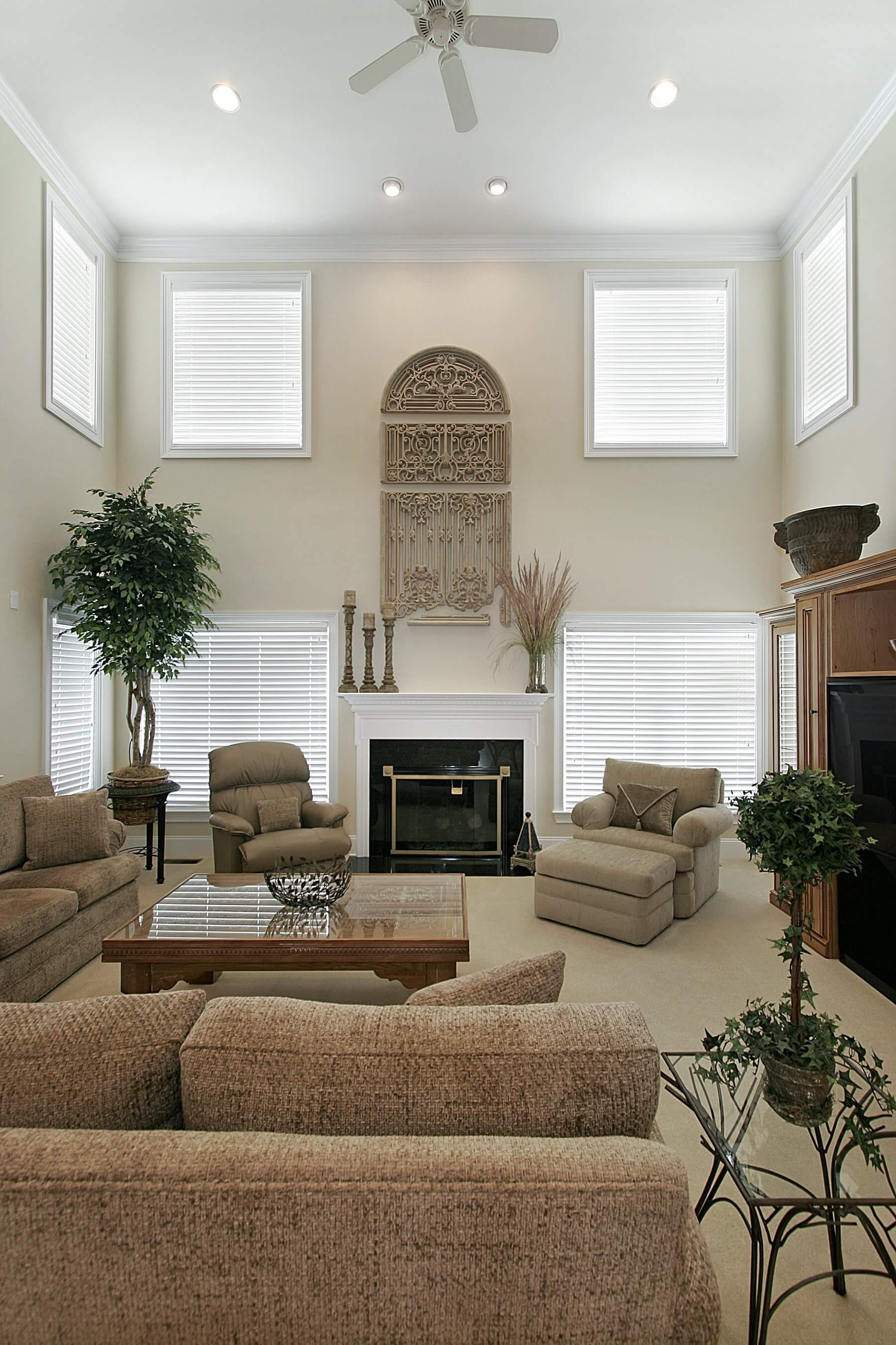 Neutral toned living room stands brown sofas and beige chairs over beige carpet, with black marble fireplace holding a white mantle, beneath the light of upper-level windows surrounding this two story room.