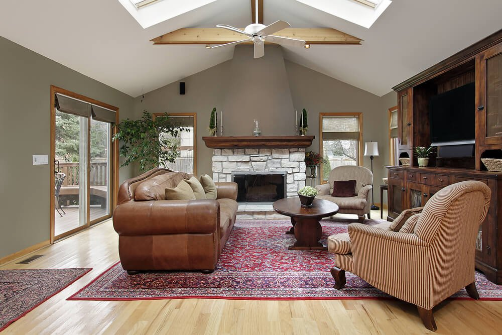 White vaulted ceiling stands over this sage colored living room, with bright natural hardwood flooring and pair of red patterned area rugs. White stone fireplace and immense dark wood entertainment cabinet stand over a pair of striped chairs and plush leather sofa with oval wood coffee table at center.