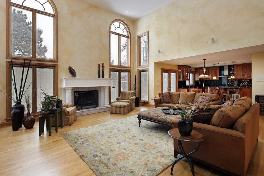 Bold white marble fireplace is flanked by floor to ceiling windows in this two story height living room. Matching brown sofas stand around wood framed ottoman coffee table on floral area rug, in an open space dominated by light hardwood flooring.